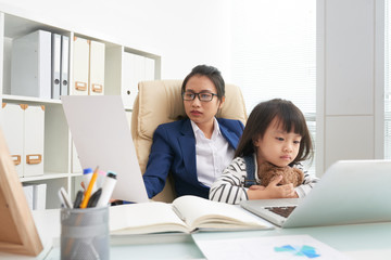 Asian woman in suit reading document while working in office with charming little daughter