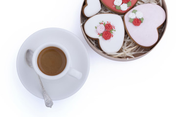 Gingerbread cookies in wooden round box and cup of coffee with spoon on white background
