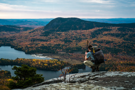 A man kneels on a mountain in Maine overlooking a lake and fall foliage while hiking the Appalachian Trail