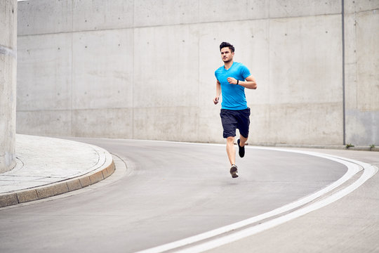 Health and fitness concept. Muscular man jogging in the city during workout session
