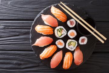 Sushi rolls set served on black stone slate on dark background. horizontal top view