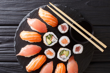 Served a set of sushi with salmon and tuna, California rolls, maki, soy sauce closeup on the table. horizontal top view