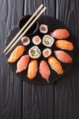Sushi rolls set served on black stone slate on dark background. Vertical top view