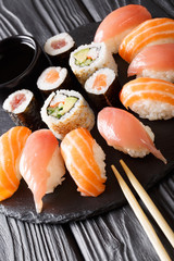 Served a set of sushi with salmon and tuna, California rolls, maki, soy sauce closeup on the table. vertical
