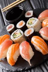 Set of sushi with salmon and tuna, California rolls, maki, soy sauce closeup on a black slate board. vertical
