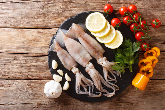 Fresh raw squid with tentacles closeup and vegetable ingredients. horizontal top view from above