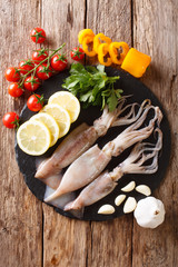 Raw fresh squid close-up and vegetable for cooking on a slate board. Vertical top view from above