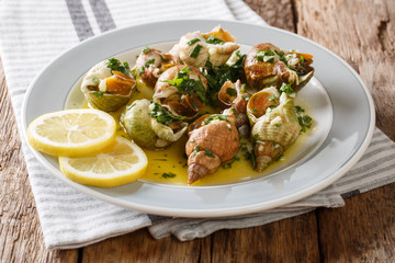 French shellfish bulot whelks served with a sauce of butter, garlic and parsley, lemon close-up. horizontal