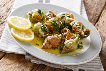 French recipe Whelks with a sauce of butter, garlic and parsley, lemon close-up. horizontal