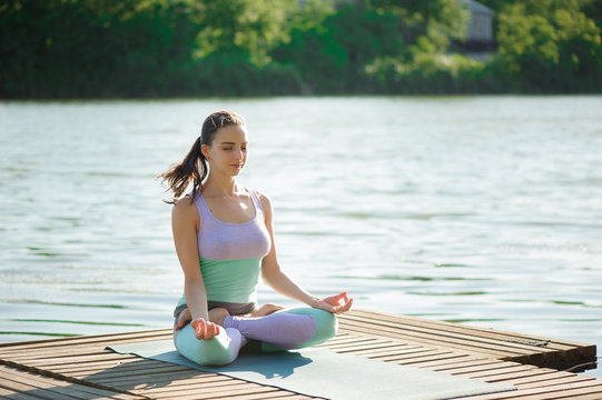 Young woman is practicing yoga at the lake