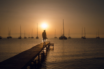 Man silhouette walking on the wooden pier on the sea bay with sailing boats and mountains on the background. Breathtaking golden sunset over the horizon.