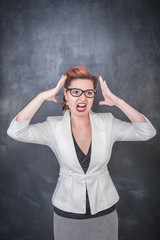 Angry screaming woman on the chalkboard background