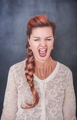 Crazy screaming woman on blackboard background