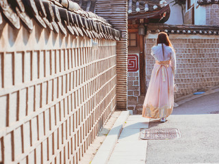 travel and tourist asia concept from backside long hair woman in korea traditional cloth (hanbok) walk in vintage town and old brick wall with soft focus background