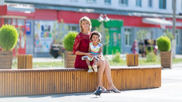 Caucasian woman with black girl sitting on a bench. Mom and daughter are resting on a bench in the town square.