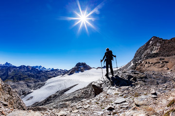 Hiker reaches a high mountain pass; he shows his joy at open arms. Val D'Aosta, Italy.