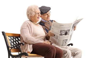 Senior couple seated on a bench reading a newspaper and laughing