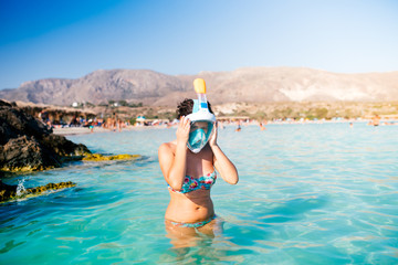 Portrait of summer girl, vacation fun woman wearing a snorkel scuba mask while swimming in ocean water. Travel holidays