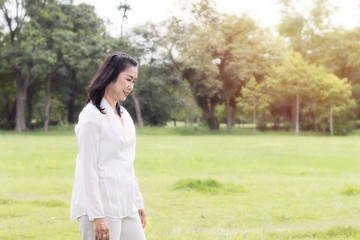 Beautiful portrait of lovely middle aged woman smiling and relaxing at the park.Copy space.