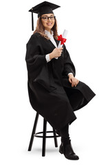 Female graduate student with a diploma sitting on a chair and smiling