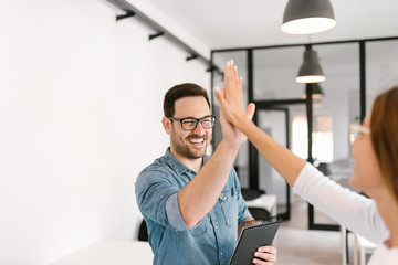Two colleagues high-five.