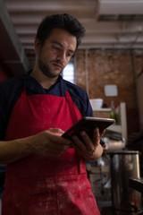 Male baker using digital tablet