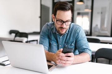 Young man using phone while sitting at desk in modern office.