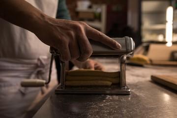 Baker using machine for preparing pasta