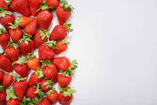 strawberry fruits on the left side on wooden background with copy space. View from above