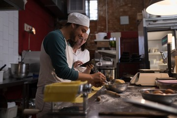 Baker preparing pasta while co-worker using digital tablet his