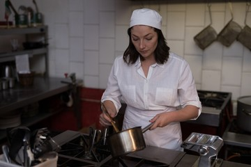 Female baker preparing food in kitchen