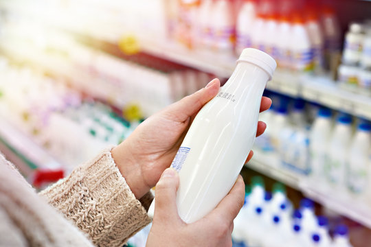 Buyer hands with bottle of milk at grocery
