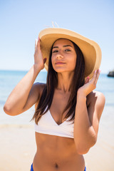 Portrait of young woman in white blue bikini on tropical beach looking at camera. Beautiful latin girl in swimwear and straw hat with copy space. Summer vacation and tanning concept.