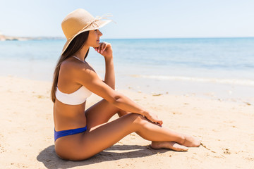 Young latin woman in straw hat lying on tropical beach