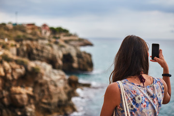 girl taking picture with phone of dramatic sea cliff with building Tarragona Spain