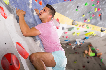 Man training at bouldering gym