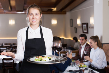 Smiling waitress with serving tray meeting restaurant guests
