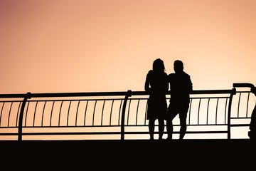 Young couple silhouettes, standing, leaning on the railing, against sunset sky.