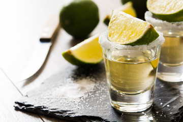 Mexican Gold tequila with lime and salt on wooden table.