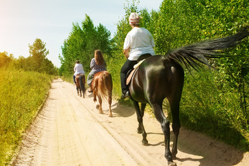 Horse ride on a summer day. A group of tourists riding a horse with an instructor