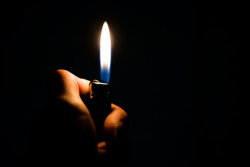 Burning lighter in the hand in the dark