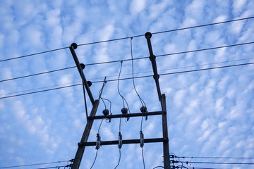 Clear blue sky with scatter clouds and electricity pole