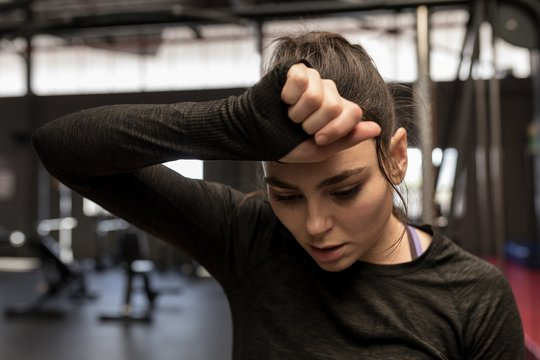 Woman wipes sweat after workout in fitness studio