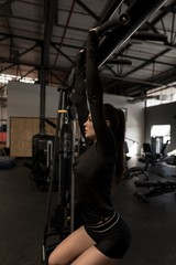 Woman doing pull ups in fitness gym