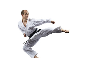 A man with a black belt trains a kick in a jump isolated