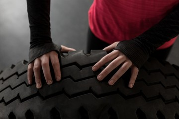 Woman exercising with tire in fitness studio