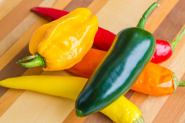 red, green, yellow and orange chillies on isolated wood background