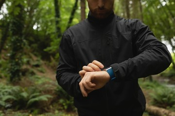 Midsection of young man looking at smartwatch in forest