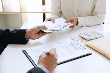 Bribery and corruption concept, bribe in the form of dollar bills, Businessman giving money in the envelope while making deal to agreement a real estate contract and financial corporate