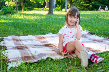 A child sits in a park on a bedspread and talks by phone.